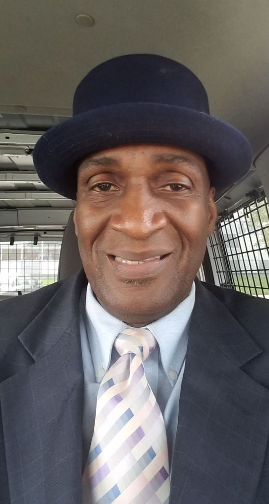 Image: A portrait photograph of Danny Franklin. He is smiling into the camera and wearing a suit and tie and a bowler cap. Photo courtesy of Danny Franklin.