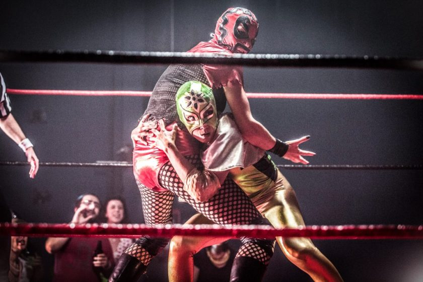 """In this still from the film """"Signature Move,"""" Zaynab (played by Fawzia Mirza) wrestles lucha libre style with Ragina Cruz (played by Molly Callinan). Zaynab faces the camera, crouching, leaning into Ragina, and gripping Ragina by the hips. Ragina's body is angled away, with right arm outspread and hand open, as if caught by surprise. Zaynab wears a green, gold, and black lucha libre mask; a shiny, stretchy, full-length bodysuit that is gold and black; and a small silver cape. Ragina wears a red and black lucha libre mask; a black mesh and shiny red top with shiny red bottoms; and black fishnets, boots, knee pads, and accessories. In the foreground and background, the ring's black and red ropes are visible. A few spectators cheer in the lower left-hand corner, and a referee's arm enters the frame from the left. The frame's edges are slightly feathered and dark."""