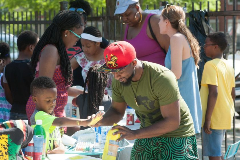 At the Bright Star block party in summer of 2018. A crowd of people stand around several tables with art materials and activities on them. The two people in the foreground are working together, holding paints, and looking down at the project they're working on. Photo by Tony Smith.