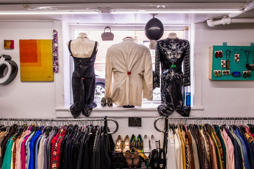 Image: A view of the inside of Gilda's store facing out towards the street. There are three mannequins in the window that are styled and displayed. From left to right, the mannequins are wearing a black jumpsuit, a cream-colored blouse, and a black and silver dress. Art and other items hang on the walls and clothes and shoes line the clothing racks on the lower half of the image. Photo by Ryan Edmund Thiel.