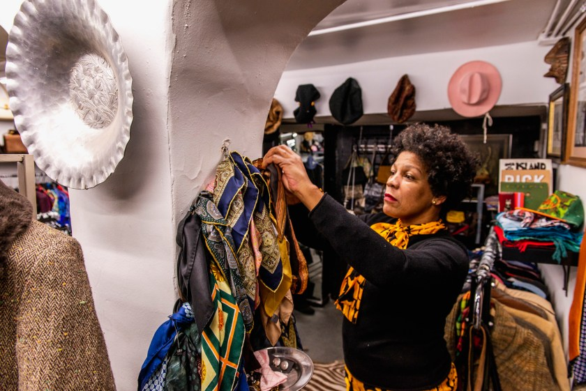 Image: A view of the interior of Gilda's, where she is seen wearing a black shirt and a yellow scarf, styling products on the wall. Several scarves hang from the walls as well as hats and other objects. Racks of clothing are in the background. Photo by Ryan Edmund Thiel.