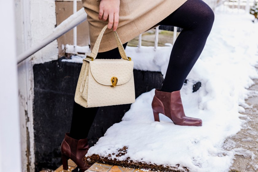 Image: A figure is walking up steps that are covered in snow. The person is carrying a cream colored purse. They are wearing burgundy high-heeled boots, black tights, and a beige skirt. Photo by Ryan Edmund Thiel.