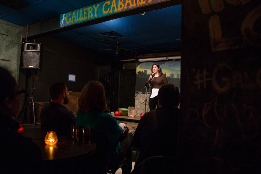"Image: Photo of Gina Watters performing at Miss Spoken at the Gallery Cabaret. The reader, wearing a dark shirt and dark pants, stands on-stage speaking into the microphone while looking out at the audience. One of Watters' hands grips the microphone and the other holds loose papers. The reader appears small near the center of the frame. Painted on the stage wall behind the reader is a scene showing Chicago's skyline, as if viewed from behind a stone wall. In the foreground, the words ""Gallery Cabaret"" are partially visible at the top of the frame. The backs and sides of some audience members' heads are visible at the bottom of the image. Photo by Sarah Joyce. Courtesy of Miss Spoken."