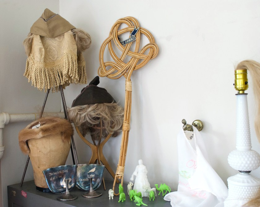 Image: A collection of objects sit on a shelf in Montgomery's studio. From left to right: a wooden wig head holds a brown fur cap; a metal stand holds a piece of fringed, beige fabric atop which sits a wedged cap with blonde hair; another metal stand holds a wedged cap with blonde hair; a wooden rug beater; small human and animal figurines; a lamp with blonde hair in the place of a lightbulb. Photo by Jessica Hammie.