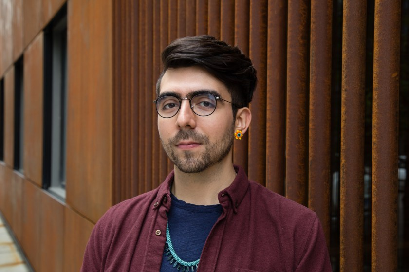 Image: Portrait of Lucas Garcia standing in front of a rust colored building. Lucas' body is angled to the left slightly and they wear a maroon button up with a navy t-shirt underneath. On their left ear is a golden flower earring.  Photo by Joshua Johnson.