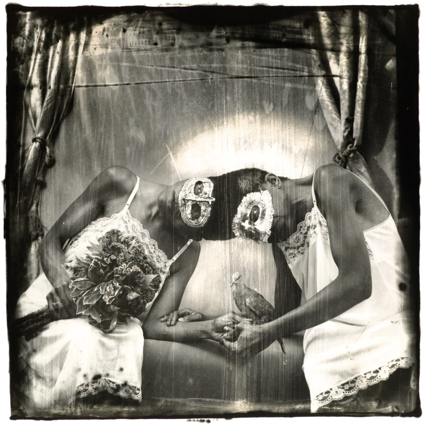Image: A black and white photograph of twins, conjoined at the top of the head, seated wearing white slip-dresses and masquerade-style masks. The woman on the left holds a bouquet of flowers while her twin on the right holds a bird. There are curtains behind them, framing the scene. Siamese Twins, Los Angeles, 1988 © Joel-Peter Witkin / image courtesy Catherine Edelman Gallery, Chicago.