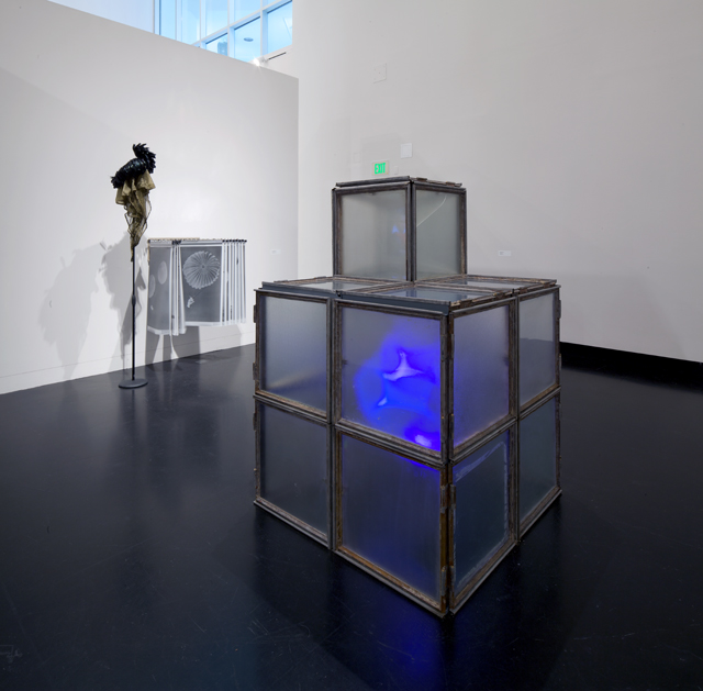 Image: Terry Adkins Recital, installation view, Tang Museum, 2012. One large, modular, square sculpture with translucent sides sits directly on the floor with a glowing blue light shining from within. In the background two sculptures can be seen, one on a stand and another mounted directly on the wall. Photo courtesy of the Mary and Leigh Block Museum, Northwestern University.