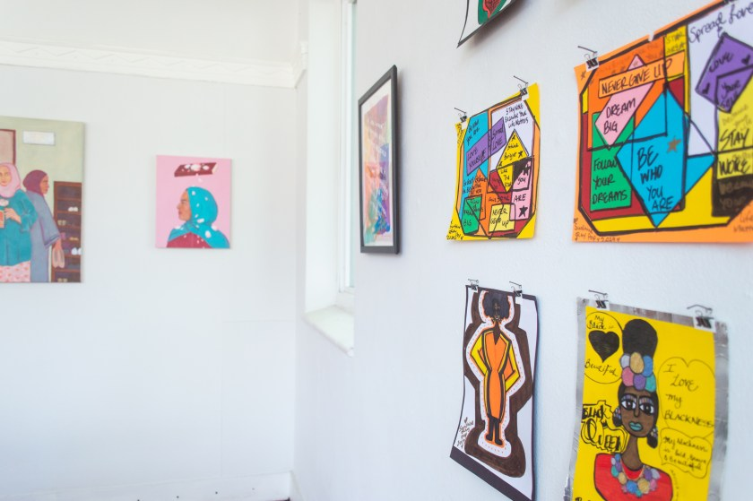 Image: Drawings, paintings, and illustrations hang on a wall at gallery space Yours Truly. The artwork is mostly figurative, with two piece on the right being mostly text-based with various shapes and colors. Photo by Cristina Ossers.