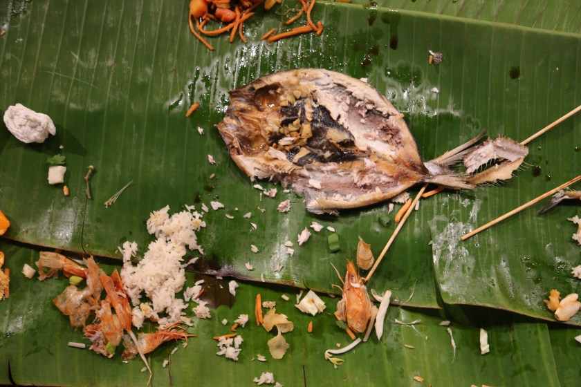 Image: Photo from Devyn's feast at Ground Level Platform shows a closeup of the food left on the green banana leaf table. Most prominently is a dismembered football-shaped fish laying flat with bits of rice scattered around it. A wadded up tissue rests on the left side of the image. Photo courtesy of artist.