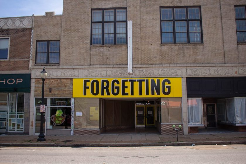 "Image: Joseph del Pesco and Jon Rubin, Monuments, Ruins and Forgetting; 2019. Installation with changing signpainting. A vacant storefront with a large yellow sign that reads ""Forgetting."" Photo by Shabez Jamal. Photo by Shabez Jamal."