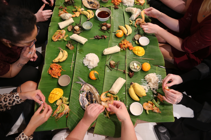 Image: Photo of Devyn's feast held at Ground Level Platform. The photo is taken from overhead and shows bright green banana leaves serving as a long table. On the leaves are various mounds and pieces of food such as a clump of white rice, halved and diced yellow mangoes, tangerines with a single green leaf still attached to them, and pairs of small and plump bananas in their peels. There are people all around the edges of the table touching the food with their hands, picking things apart. Photo courtesy of the artist.
