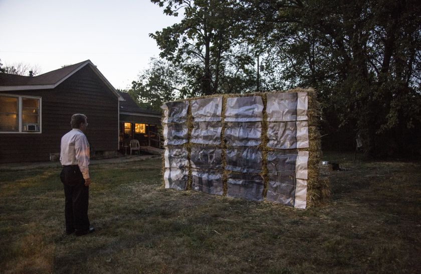 Image: Documentation image of Cass Davis' Witness, 2017 taken at sunset. The piece is made up of 30 hay bales, bailing twine, and an archival reproduction of a photograph from the 1908 Springfield Race Riot. Hay bales are stacked horizontally and vertically to achieve height. The archival photograph has been enlarged and cut into 16 even-sized rectangles and attached to the hay bales with twine. The piece is displayed on a vacant lot of grass with trees in the background and a house in the neighboring lot. A man wearing black pants and a long sleeve collared shirt faces the installation. Photo by the artist. Archival photograph courtesy of the University of Illinois, Springfield Archives.