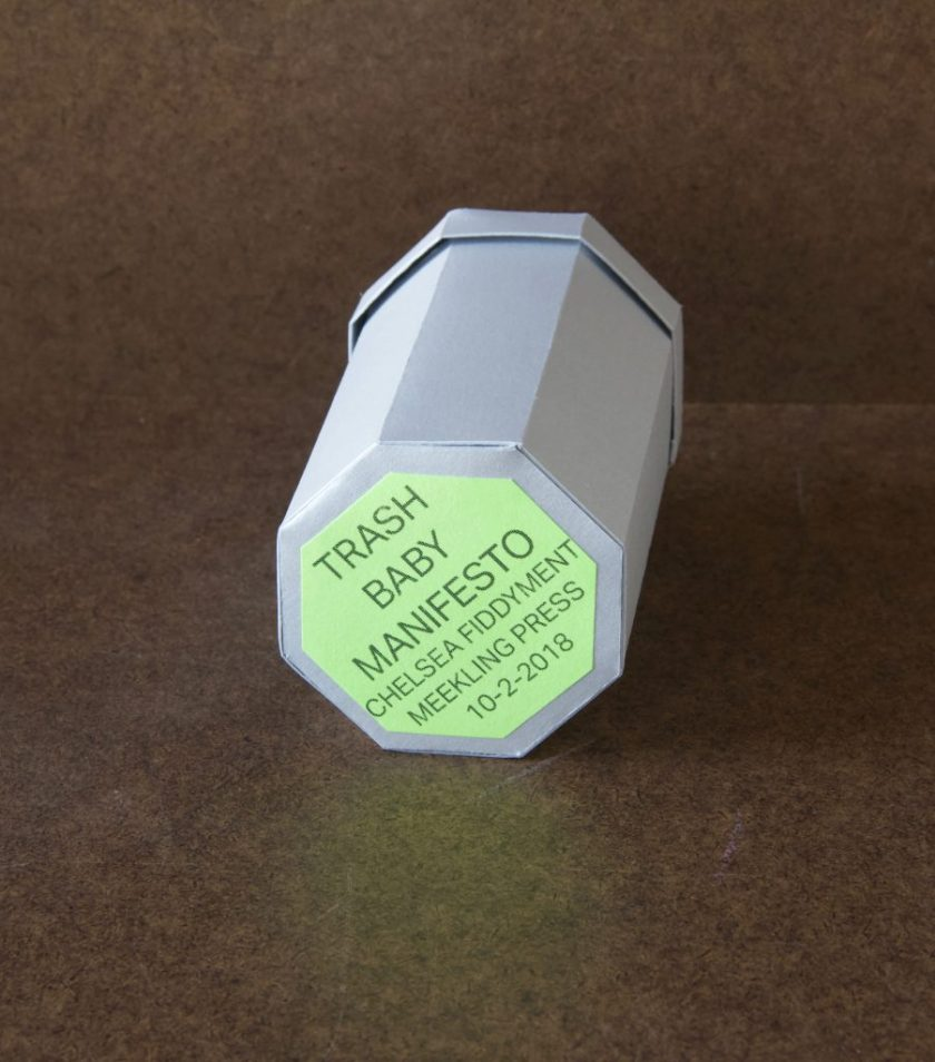 "Image: A photo of ""Trash Baby Manifesto,"" a book by Chelsea Fiddyment, 2018. The book's casing looks like a trashcan — octagonal at the base and top, with a lid. It is made out of thin white cardboard. The focal point of the image is the bottom of the trashcan, where a light green octagonal sticker reads, in all capital letters, ""Trash Baby Manifesto, Chelsea Fiddyment, Meekling Press, 10-2-2018."" The book sits on a dark surface. Photo by Meekling Press. Courtesy of the artist."