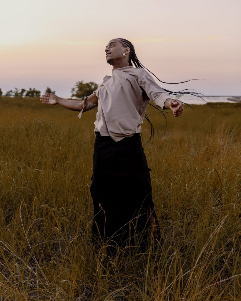 Image: Morenxxx stands in the grasses with their arms outstretched and whips their braids around their head. Photo by Ryan Edmund.