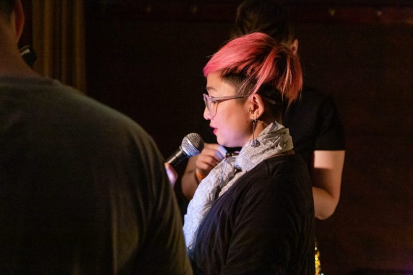 Image: Dao Nguyen performing at Unreal at Schubas. Nguyen stands in profile, lit brightly and speaking into the microphone. Two other performers, standing on either side of her, are only partially visible in the frame. Nguyen wears a black shirt with a silver scarf and pink glasses a few shades lighter than her hair. Photo by Joshua Clay Johnson.