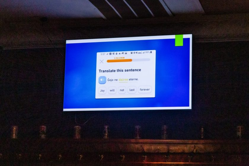 "Image: An excerpt of a piece by Jerliyah Craig (not present), comprised of presentation slides being advanced by Chelsea Fiddyment (out of frame) at Unreal at Schubas. Against a blue background, this slide shows a phone screenshot of a translation activity from the app Duolingo, with the same sentence in Esperanto (""Ĝojo ne daŭros eterne"") and English (""Joy will not last forever""). The slides are being presented on a flat-screen monitor, above and below which parts of the wall and ceiling are visible. The room's lights are off. Photo by Joshua Clay Johnson."