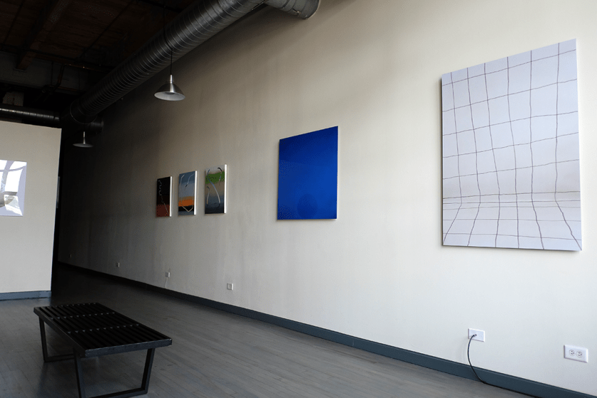 Image: FLXST Gallery. Against an eggshell wall, from right to left, Gina Osterloh's Drop Shadow, then Orifice, Holding Space (Blue), then Roberto Jamora's Manila Plaza, Lake Borgne, and Bayou St. Malo. Opposite the wall, on the floor is a backless black bench seated parallel to the artwork. There are two silver lamps hanging from the ceiling and four outlets distanced along the wall. Image courtesy of FLXST Contemporary.