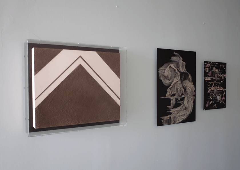 Image: Three images hung on a white wall. Left, Kat Larson's Untitled (Dirt Painting) contained by a glass pane. To the right are Kiam Marcelo Jiam's Sheath and Pink Panagnip. Image courtesy of FLXST Contemporary.