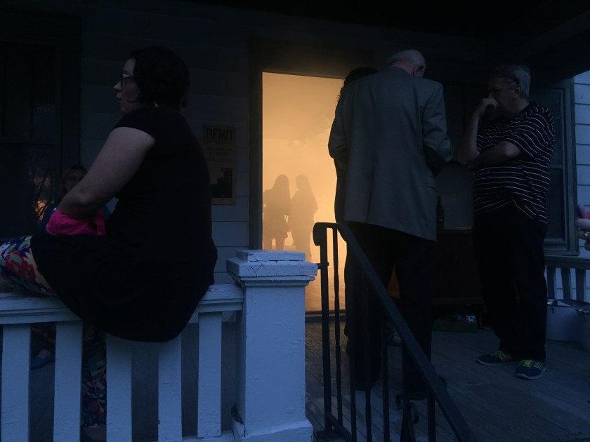 Image: Reception and entrance to Nobody's Home by Lyndon Barrois Jr., Addoley Dzegede, Cole Lu, and Catalina Ouyang. DEMO Project, May 2017. In the foreground, a few visitors linger on the front porch at dusk. Through the open doorway in the background, two figures stand viewing the exhibition through the orange haze. The Image courtesy of Lyndon Barrois Jr.