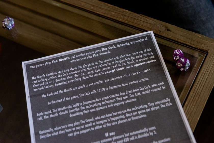 "Image: A close up of a piece of paper with a black background and white text explains the game, ""Welcome to Paradise, Baby"" where one player is The Mouth, the other player is The Cock and observers, like our staff photographer, was The Crowd. To the right side of the paper are two die. Photo by Ryan Edmund Thiel"