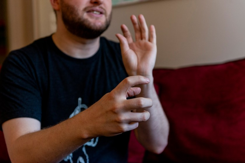 Image: The image is focused on the artists hands. The hand in focus and closest to the viewer is grasping something while the left hand is in motion towards the artists face. Photo by Ryan Edmund Thiel.