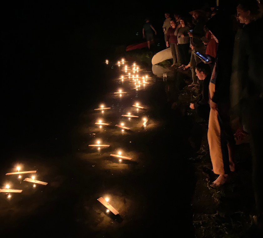 Image: Over twenty Wishboats (floating pieces of wood holding candles) are floating in water in a dark, nighttime scene. The candlelight illuminates figures standing on the shore to the right of the frame. Photo by Rachel Hausmann Schall.
