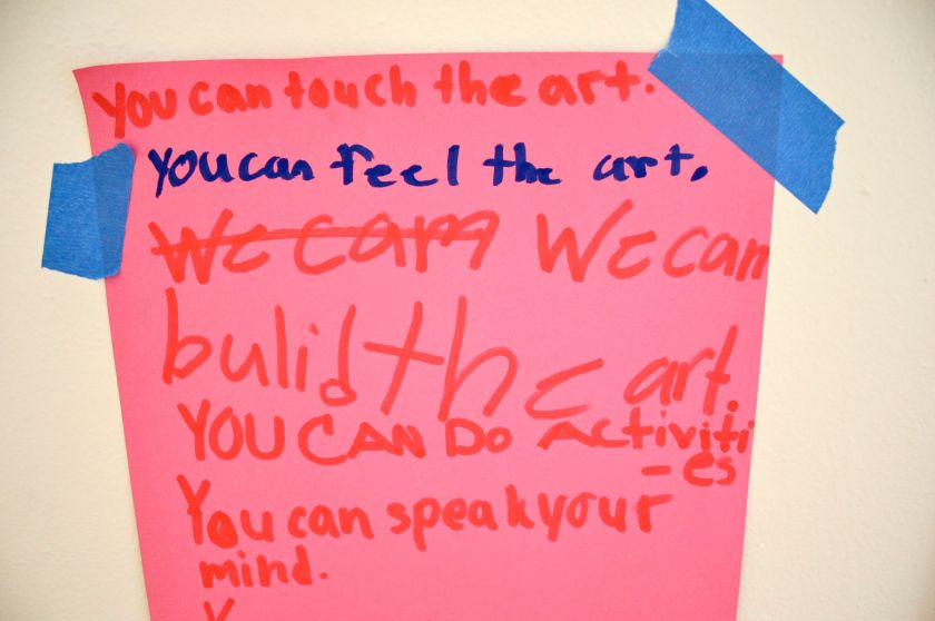 "Image: A sign at Pink House, St. Louis. The sign is bright pink and reads, in red and blue marker, in a child's handwriting: ""You can touch the art. You can feel the art. We cam We can build the art. You can do activities. You can speak your mind."" The sign is attached to a white surface using blue tape. Photo by Patrick Fuller. Courtesy of the artist."