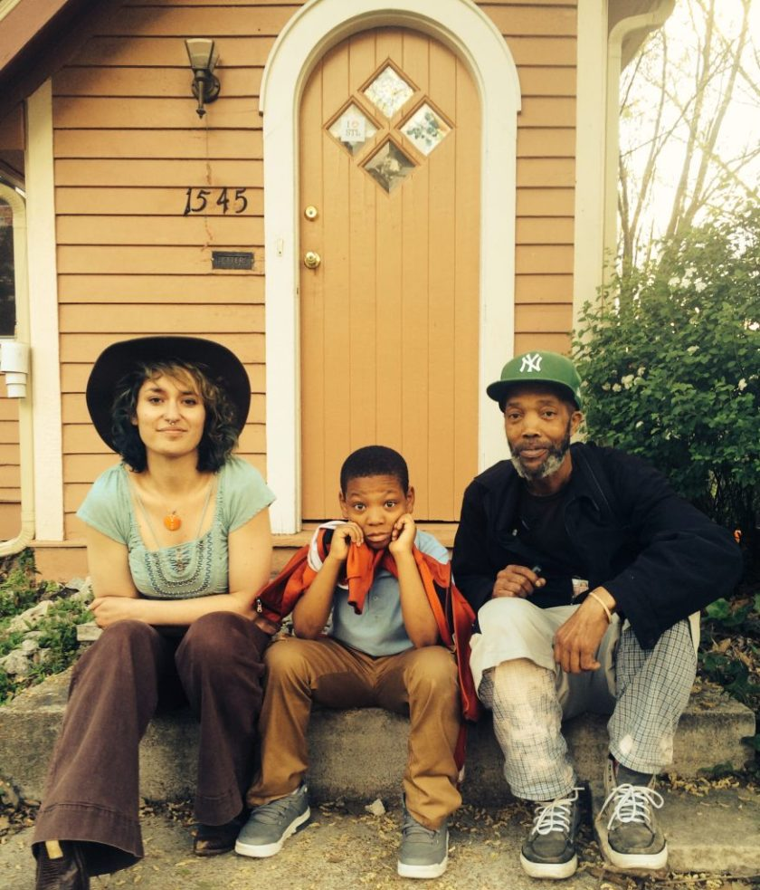 Image: Regina Martinez at Pink House in St. Louis in April 2016, with Javontá Fletcher and Curtis Lomax (left to right). The three sit on Pink House's concrete front step, posing for the camera. Martinez wears a broad-brimmed hat, a patterned sea-foam green shirt, and brown pants; Fletcher wears a light blue shirt and brown pants, and holds an orange jacket around his shoulders; Lomax wears a black jacket, light shorts over light plaid pants, and a green New York Yankees cap. Martinez and Lomax are adults and Fletcher is a child. Photo by Joy Southerland. Courtesy of the artist.