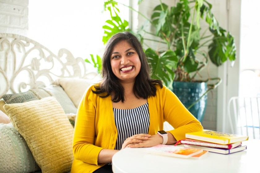 """Featured image: Sharanya Sharma. Sharma sits with hands folded on a white table, with copies of """"Set Fire to This Crooked House"""" and multi-colored notebooks in the foreground. Sharma wears a marigold cardigan open over a black and white striped shirt and smiles at the camera. Behind Sharma are several pastel throw pillows and a large plant, and natural light comes through the windows. Photo by Kristie Kahns Photography."""