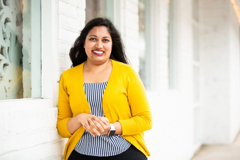 Image: Sharanya Sharma. Sharma leans against the outside of a white brick building, smiling at the camera. Sharma wears a marigold cardigan open over a black and white striped shirt, and Sharma's hands are folded. Photo by Kristie Kahns Photography.