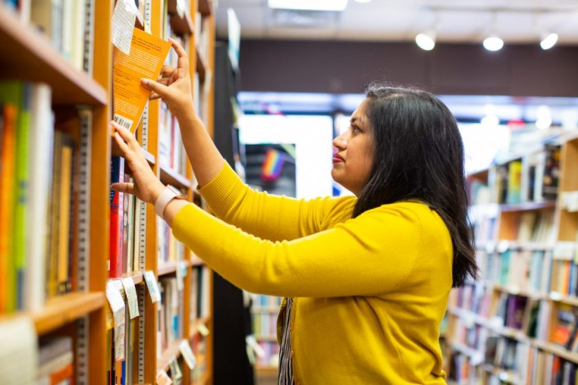 Image: Sharanya Sharma. Sharma stands in profile inside a bookstore, with one hand pulling a book off a shelf and the other hand resting on the same shelf. Sharma wears a marigold cardigan open over a black and white striped shirt. The bookstore is bright with daylight, and tall shelves are visible on the left and right sides of the frame. Photo by Kristie Kahns Photography.