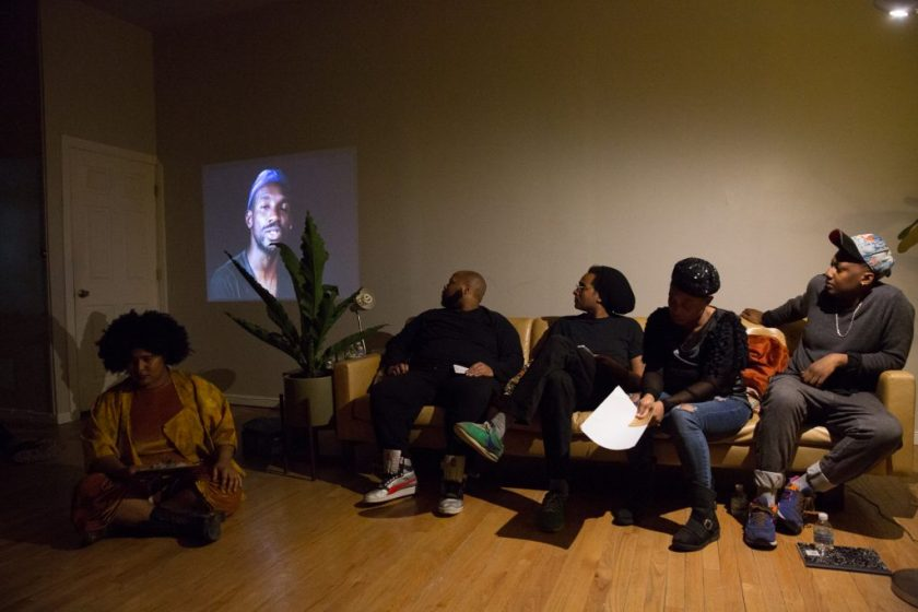 "Image: In-Session, ""Eclipsing: Migration, Movements and Desire,"" at Threewalls in March 2018, presented by Amina Ross with J'Sun Howard, Khadijah Ksyia, Jared Brown, and A.J. McClenon, in response to the guiding work ""Tongues Untied"" by Marlon Riggs. In this shot, the artists sit in a row, with an image from ""Tongues Untied"" projected on the wall behind them in a low-lit room. Ross (left) sits on the wood floor and Howard, Brown, Ksyia, and McClenon (left to right) sit on a tan couch. Howard, Brown, and McClenon look toward the projected video and Ross and Ksyia look down. Ross wears a mustard-colored one-piece and jacket, Howard and Brown both wear all black, Ksyia wears a black top with blue jeans, and McClenon wears a grey top with grey jeans. Brown, Ksyia, and McClenon all wear headwear, and Ksyia holds paper in hand. Photo by Milo Bosh. Courtesy of Threewalls."