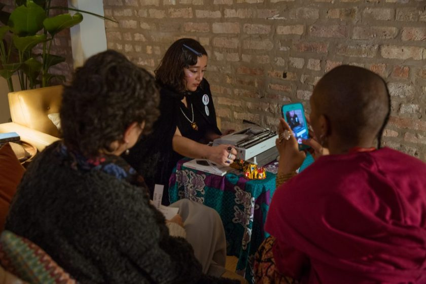 "Image: In-Session, at Threewalls in November 2018, by Najee Searcy and collaborators, in response to the guiding work ""Hush: Don't Say Anything to God: Passionate Poems of Rumi"" by Shahram Shiva. Melissa Castro Almandina sits at a small table that is covered in a colorful tablecloth, looking down at a typewriter while turning the knob to advance paper through it. Also on the table is a copy of Claudia Rankine's book, ""Citizen: An American Lyric,"" and small sculptural objects that are primarily yellow, brown, and red. The artist wears a similar object as a pendant. The artist wears black clothes, as well as multi-colored rings, buttons, and hair clips. In the foreground, with their backs to the camera, sit two people, one using a phone to take a photo of the artist and the other holding slips of paper with text on them. Photo by Milo Bosh. Courtesy of Threewalls."