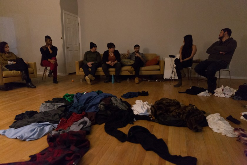 "Image: In-Session, at Threewalls in February 2018, by Jose Luis Benavides and collaborators, in response to the guiding work ""Mexican American Disambiguation"" by José Olivarez. In the background, seven people sit on chairs or a tan couch, all looking towards the center, at Benavides, who is speaking. In the center of the low-lit room — in the foreground and around the image — is a sprawling pile of clothes. Photo by Milo Bosh. Courtesy of Threewalls."