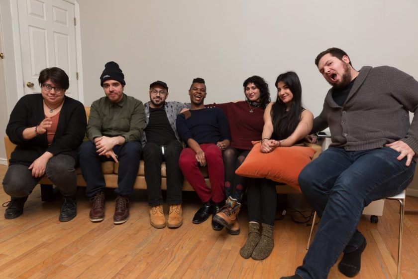 """Image: In-Session, at Threewalls in February 2018, by Jose Luis Benavides and collaborators, in response to the guiding work """"Mexican American Disambiguation"""" by José Olivarez. After the performance and discussion, Regina Martinez (third from right) and six others (performers) sit together on or near a tan couch, smiling or making faces at the camera. Martinez wears a maroon top with dark leggings and boots. Photo by Milo Bosh. Courtesy of Threewalls."""