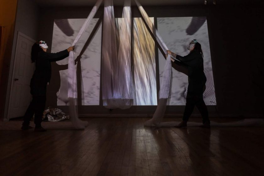 """Image: In-Session, at Threewalls in March 2019, by Maya Mackrandilal with collaborators Udita Upadhyaya and Enid Muñoz and original performance for video by Bhanu Kapil, in response to the guiding work """"Schizophrene"""" by Bhanu Kapil. In this wide shot, Muñoz (left) and Mackrandilal (right) perform. Both stand near a far wall, wearing black clothes and white masks with multi-colored decorations, looking up at a very long, diaphanous white cloth that is attached to the ceiling above them in two places with its middle portion hanging low between them. Each performer holds one part of the white cloth, with each end of its remainder snaking off-camera to the left and right behind each performer. A wall-sized video, showing a textured white scene, is projected over the performers and the cloth. Balled up in one corner of the floor is a silver reflective cloth. Photo by Milo Bosh. Courtesy of Threewalls."""