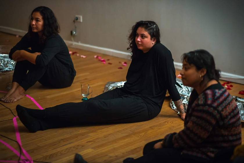 "Image: In-Session, at Threewalls in March 2019, by Maya Mackrandilal with collaborators Udita Upadhyaya and Enid Muñoz and original performance for video by Bhanu Kapil, in response to the guiding work ""Schizophrene"" by Bhanu Kapil. Muñoz (left), Mackrandilal (center), and Upadhyaya (right) sit on the wood floor during the discussion portion of the event. They sit in oblique profile to the camera, looking off-camera toward the audience in the low-lit room. Muñoz and Mackrandilal both wear all black, and Upadhyaya wears a patterned sweater with dark bottoms. A length of fluorescent pink ribbon sits in the lower-left corner of the frame. Photo by Milo Bosh. Courtesy of Threewalls."