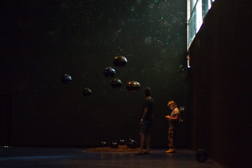 "Image: Viewers interacting with ""Dark Matter: Celestial Objects as Messengers of Love in These Troubled Times"" by Folayemi Wilson at the Hyde Park Art Center. The installation has made the space very dark with hanging orbs towards the middle of the frame. Photo by Michael Sullivan."