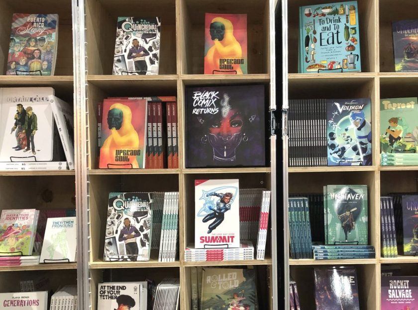 Image: The Black Comix Returns book sits on a wood bookshelf surrounded by other books, mostly graphic novels, at San Diego Comic Con 2019. The Black Comix Returns cover is various shades of purple and features a drawing of a woman's face, with pink across the bridge of her nose and her cheeks. The artwork on the cover is by Ashley A. Woods. Photo by Jessica Hammie