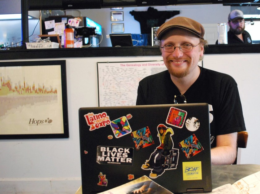 Image: Damian Duffy is seated at a table in a brewery. He is smiling and looking at the camera. In front of him is a laptop computer, covered in stickers. Photo by Jessica Hammie.