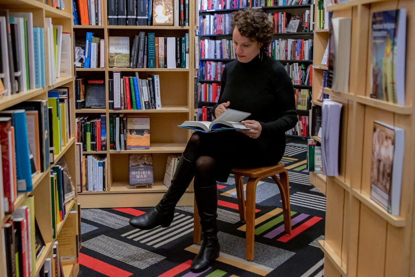 Image: Mustafah sits in a wooden chair inside a bookstore, browsing through an open book in her lap. She wears a long-sleeved black turtleneck dress, black tights, black boots, and large hoop earrings. Bookshelves full of books are behind and around her, positioned at various angles. The carpet's pattern is a grid of thin and thick stripes in black and white and bright colors. Photo by Mark Blanchard.