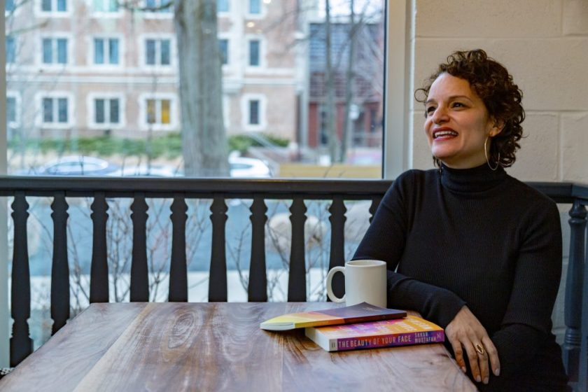 Image: Mustafah sits at a wooden table, looking off-camera and laughing. In the foreground are a coffee cup and two books, her short story collection and her debut novel; the books' covers are a mix of mostly yellows, oranges, pinks, and browns. Mustafah wears a long-sleeved black turtleneck and large hoop earrings. Behind her is a Hyde Park street, and natural light comes through the window. Photo by Mark Blanchard.