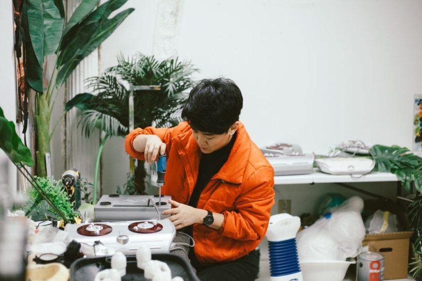 Rachel Youn in their studio hacking a massager with a screwdriver. Photo by Krista Valdez.