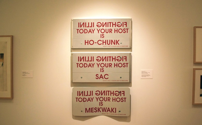 "Image: Hock E Aye Vi, Edgar Heap of Birds, ""Beyond the Chief,"" 2008. Three steel panels are arranged vertically; the bottom one is bent. On each panel the words ""Fighting Illini"" appear as a mirrored image, followed below by the phrase ""today your host is"". Each panel then names  a different Native American tribe: from top to bottom, Ho Chunk; Sac; Meskwaki. Photo by Jessica Hammie."