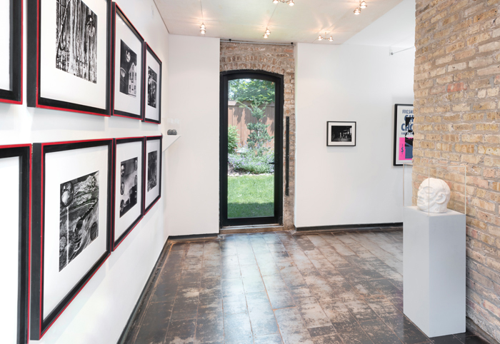 "Image: Installation shot of Iceberg Projects exhibition ""David Wojnarowicz: Flesh of My Flesh,"" June 23 – August 5, 2018. On the left wall, a series of images are hung in rows. A sculpture of a head is encased in glass on the right way. Directly in front of the viewer, an outdoor green space is visible through a glass door. Image courtesy of Iceberg Projects."