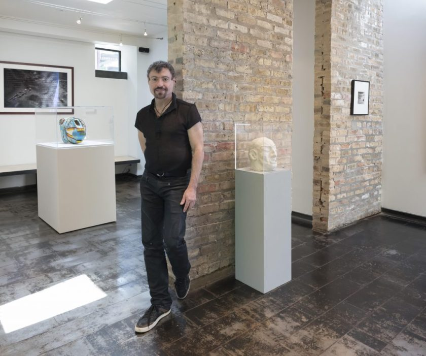 Image: Dr. Dan Berger standing against a partial brick wall in the Iceberg Projects exhibition space. He is wearing dark jeans and a black short-sleeve shirt. Image courtesy of the artist.