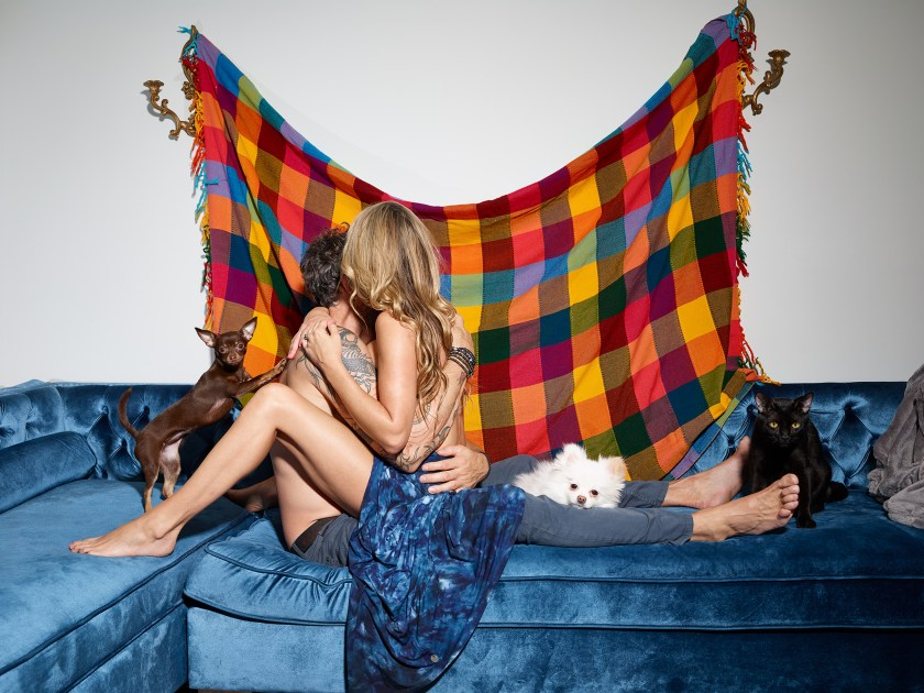 Image: Vermillion, 2020 by Marzena Abrahamik. A photograph of two people hugging with one sitting on top of the other on a blue couch. There are several dogs and a cat in the photo. A blue, yellow, and orange plaid blanket is draped on the wall behind the two people. Image courtesy of the artist.
