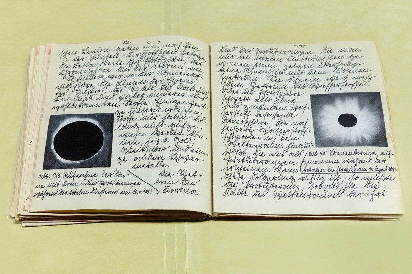 Image: Werner von Braun's Astronomy Manuscript, Written at Age 15, 1927/2019 by Barbara Diener. A photograph of an open journal with German writing on both pages and black and white photos of the moon. Image courtesy of the artist.