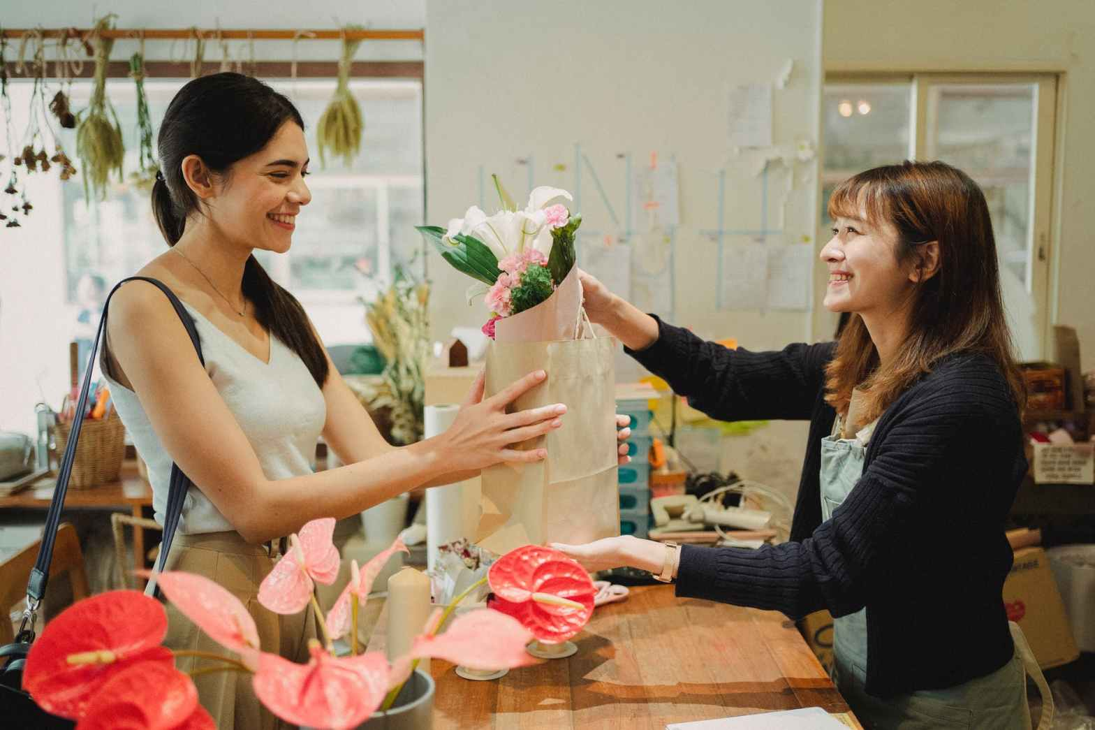 happy florist giving bouquet of flowers to lady