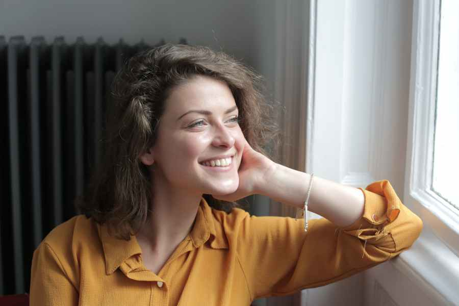 happy young woman looking out window at home